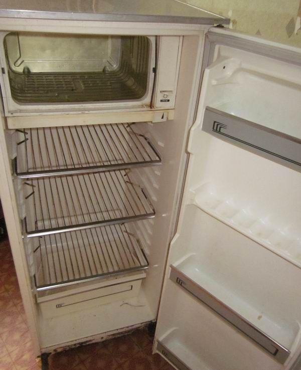 Старий холодильник з відчиненими дверцятами