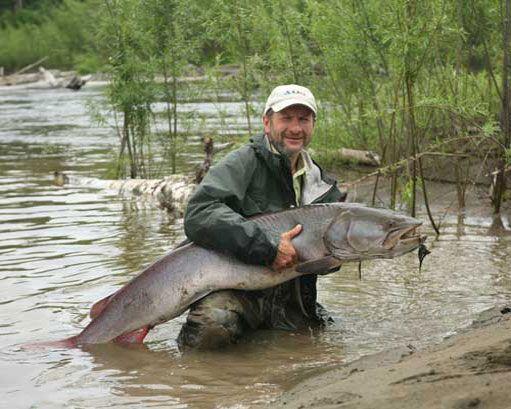 Рибак тримає в руках тайменя